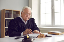 Wise Senior Lawyer In Glasses Working With Case Documents In Office. Serious Mature Judge In Gown Uniform Reading Book While Sitting At Table In Court Of Law. Concept Of Judicial System And Justice