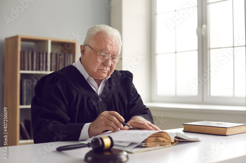 Canvas Print Wise senior lawyer in glasses working with case documents in office