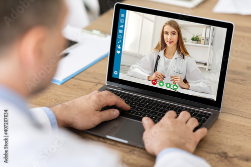 Obraz Online medical consultation. Male patient communicating to his doctor on laptop at home - fototapety do salonu