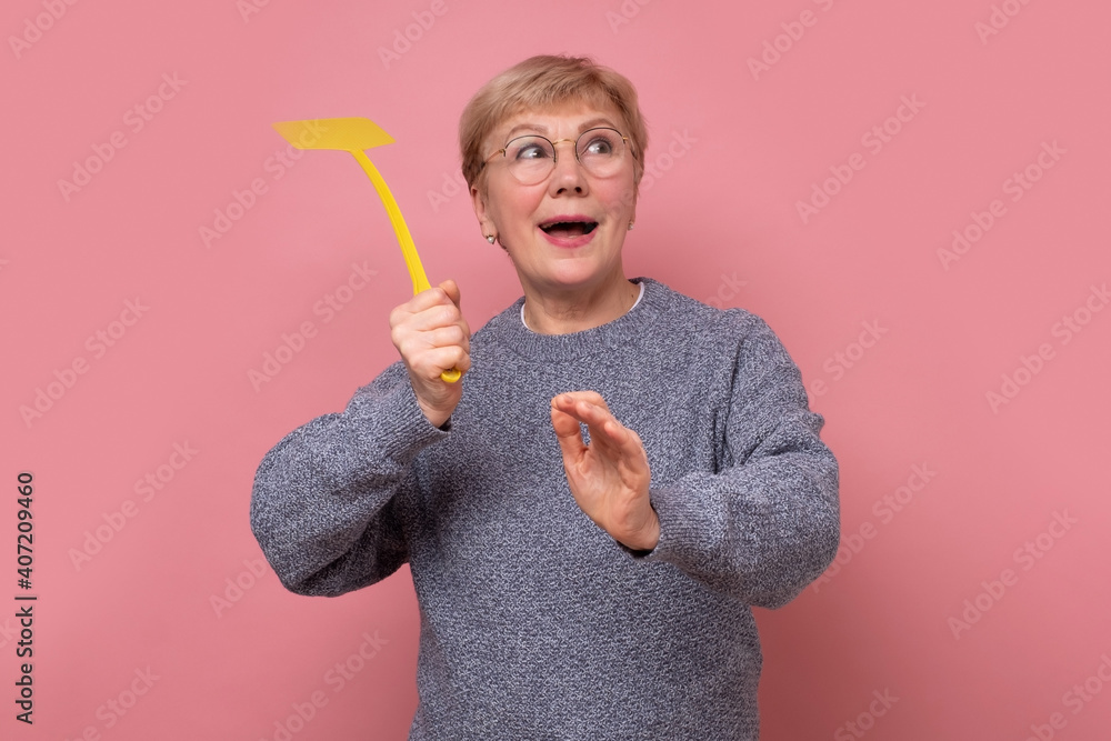 Fototapeta Caucasian senior woman with fly swatter trying to kill a mosquito.