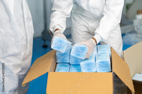 Fototapeta Workers are packing masks in boxes for delivery to customers