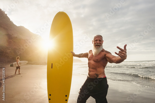 Fototapeta Happy fit senior having fun surfing at sunset time - Sporty bearded man training with surfboard on the beach - Elderly healthy people lifestyle and extreme sport concept obraz