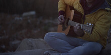 A Guy On The Street In A Yellow Jacket Sits And Plays The Guitar