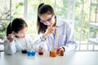 Blurred soft images of pretty Asian teacher is teaching a 6 year old girl, about scientific experiments On white table in a science lab classroom, to children and education concept.