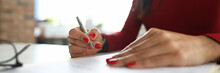 An Employee In A Red Dress Makes Notes. The Woman Is Focused On The Effectiveness Of The Companys Business Processes