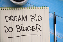 Dream Big Do Bigger, Text Words Typography Written On Book Against Wooden Background, Life And Business Motivational Inspirational