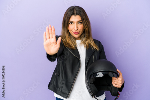 Fotografie, Obraz Young indian motorbiker woman isolated standing with outstretched hand showing stop sign, preventing you