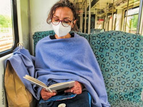 ein frau mit gesichtsmaske liest ein buch © ArTo