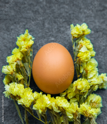 Obraz Easter egg and yellow flowers on a gray background. Color trend 2021. Vertically - fototapety do salonu