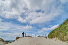 Back View Of An Unidentifiable Person Under Vivid Blue Sky With White Clouds  In The Sand Dunes Of The North Sea Coast In Nymindegab Strand, Denmark