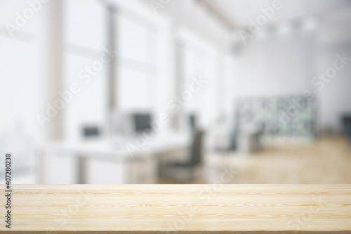 Obraz Blank tabletop made of wooden planks with light contemporary furnished office on background, mockup - fototapety do salonu