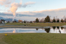 A Lone Canadian Goose Stands By A Small Pond Water Hazard On A Golf Course In A Golf Course Community Of Homes In Post Falls, Idaho, USA