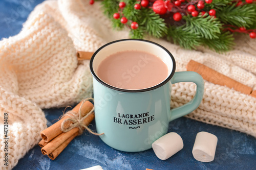 Tasty hot cocoa with cinnamon and marshmallow in cup on color background © Pixel-Shot