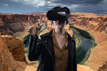Woman Wearing A Virtual Reality Headset In A Simulated Hiking Experience Through The Desert.  VR Tourism Is A Digital Outdoor Simulation While Staying At Home