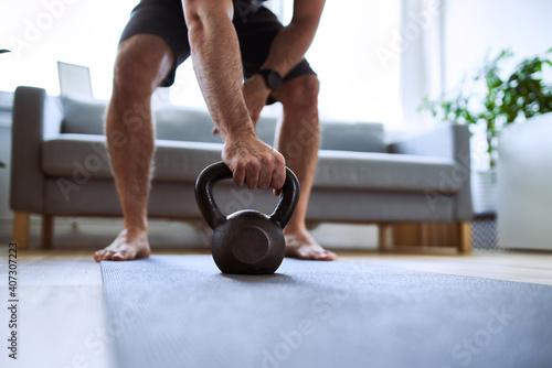 Fototapeta Closeup of man grabing kettlebell during home workout exercises obraz
