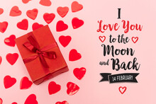 Top View Of Red Paper Hearts And Gift Box Near I Love You To The Moon And Back, 14 February Lettering On Pink Background