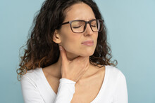 Woman Having Sore Throat, Tonsillitis, Feeling Sick, Suffering From Painful Swallowing, Angina, Strong Pain In Throat, Loss Of Voice, Holding Hand On Her Neck, Isolated On Studio Blue Background.