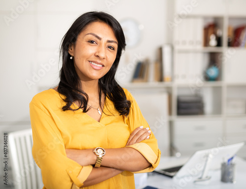 Tableau sur Toile Happy smiling Latin American businesswoman standing in office with arms crossed