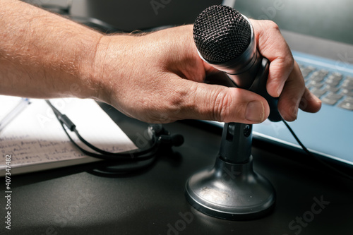 Photo A man's hand accommodating a desktop microphone before a virtual conference