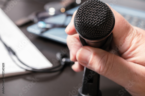 Canvas Print A man's hand accommodating a desktop microphone before a virtual conference