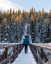 Man In A Blue Jacket, Black Pants Walking Across A Snowy, Snow Covered Bridge In Winter Time With Boreal Forest And Winter Skies, Blue Sky In Background In Miles Canyon, Yukon.