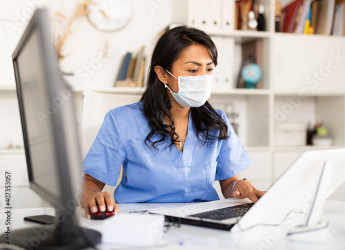 Obraz Smiling peruvian female therapist working with case histories on laptop in modern medical office - fototapety do salonu