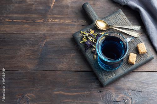 Thai blue tea anchan of buds klitoria Ternate in a glass cup, dark background. Copy space © Elenglush