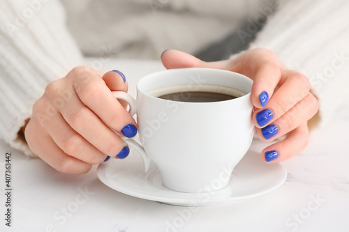 Obraz na plátně Woman with beautiful manicure and cup of coffee on table, closeup