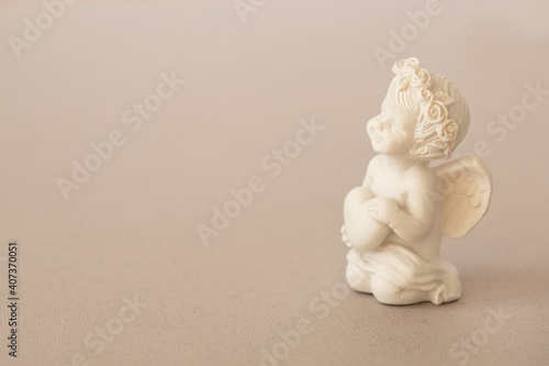 Foto figurine of an angel Cupid with a bow on a pink background