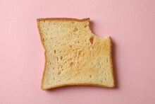 Bitten Toast Bread On Pink Background, Close Up