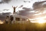 Fototapeta Miasto - Man with raised arms on the roof of his camper van