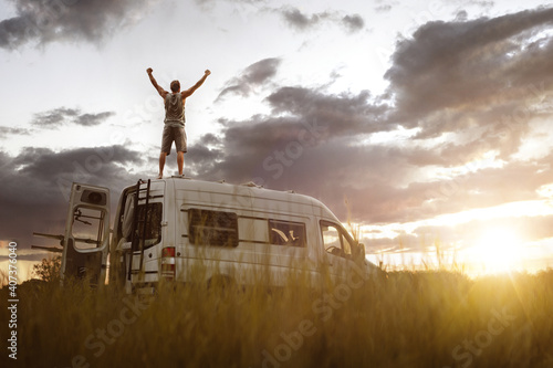Man with raised arms on the roof of his camper van - fototapety na wymiar