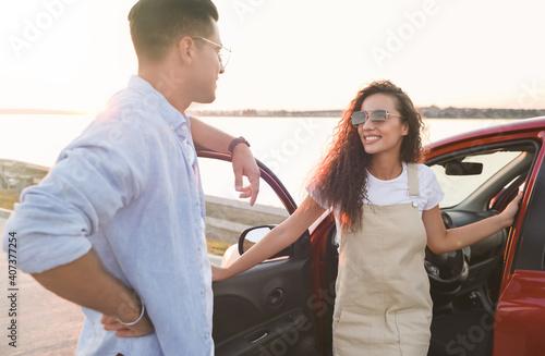 Fotografie, Obraz Happy couple near car outdoors at sunset. Summer trip