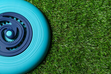 Light Blue Plastic Frisbee Disk On Green Grass, Top View. Space For Text