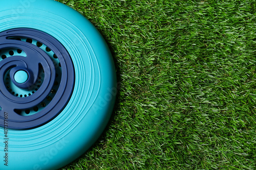Canvas Print Light blue plastic frisbee disk on green grass, top view