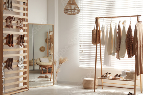 Fotografering Modern dressing room interior with racks of stylish women's clothes and shoes