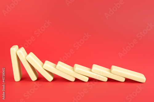 Obraz White domino tiles falling on red background. Space for text - fototapety do salonu