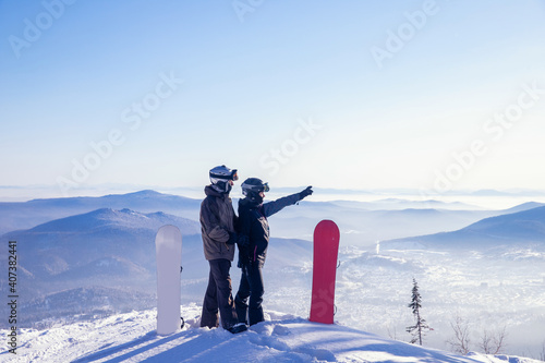 Obraz Loving couple of snowboarders hold hands and look forward, man indicates direction to woman with snowboard route with hand - fototapety do salonu