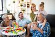 Leinwandbild Motiv Senior grandparents playing with grandchildren and having fun with family