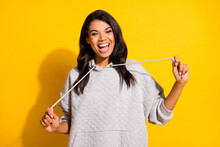 Photo Of Happy Nice Afro American Woman Hold Hoodie Laces Good Mood Smile Isolated On Yellow Color Background
