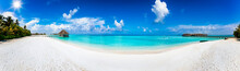 Wide Panoramic View Of A Tropical Beach With Turquoise Sea, Palm Trees And Water Lodges Over The Ocean In The Maldives Islands