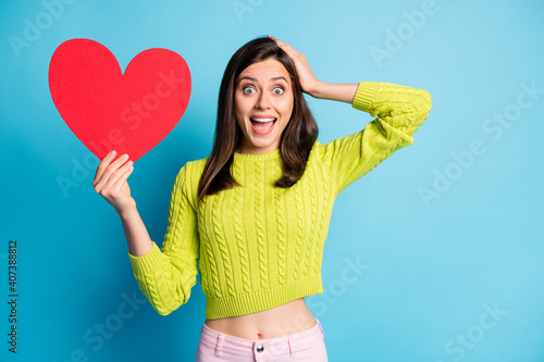 Photo portrait of shocked screaming woman holding heart head with one hand isolated on pastel blue colored background