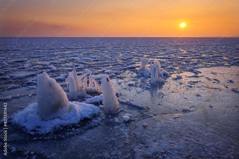 Fototapeta Sunrise and frozen sea. Beautiful winter landscape with lake in morning time. Daybreak