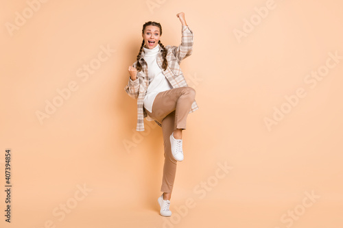 Obraz Full size photo of hooray nice girl hands fists wear white shirt trousers sneakers isolated on beige color background - fototapety do salonu
