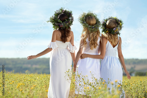 Fototapeta Young women wearing wreaths made of flowers in field on sunny day, back view