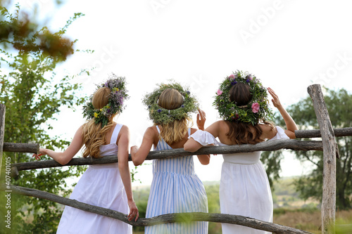 Obraz na plátně Young women wearing wreaths made of beautiful flowers near wooden fence, back vi