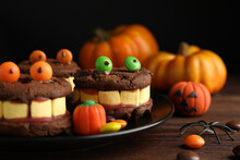 Delicious Desserts Decorated As Monsters On Wooden Table, Closeup. Halloween Treat