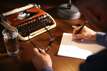 Man Writing Letter At Wooden Table Indoors, Closeup
