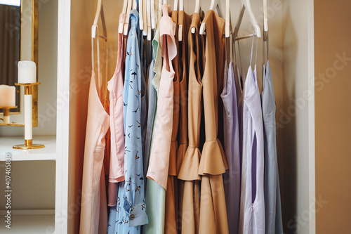 Fotografering Women's clothing dresses and blouses on hangers in a dressing room or store