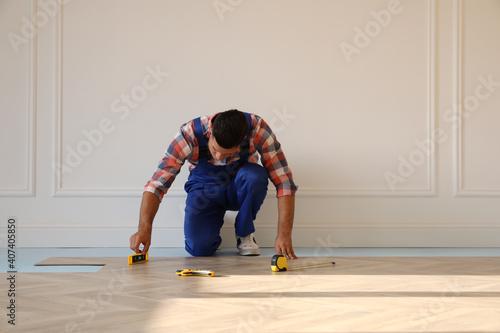 Obraz Professional worker installing new parquet flooring indoors - fototapety do salonu